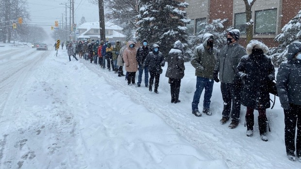 Front-line workers wait in long, snowy line for COVID-19 vaccine due to 'minor booking issue'